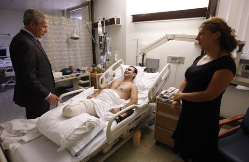 President George W. Bush speaks with Sgt. Besiki Balakhadze, a member of the Georgian Army Coalition Forces, during a visit Tuesday, Sept. 9, 2008, to Walter Reed Army Medical Center in Washington, D.C., where the soldier is recovering from wounds received during Operation Iraqi Freedom. With them is interpreter Staff Sgt. Tatiana Ivanova, also of the Georgian Army Coalition Forces. White House photo by Eric Draper