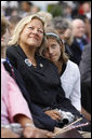 A young girl leans close to her mother during the dedication ceremony of the 9/11 Pentagon Memorial Thursday, Sept. 11, 2008, in Arlington, Va. White House photo by Eric Draper