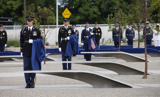 Soldiers hold ceremonial cloths that were draped over the 184 memorial benches, each honoring all innocent life lost when American Airlines Flight 77 crashed into the Pentagon on Sept. 11, 2001, during the dedication of the 9/11 Pentagon Memorial Thursday, Sept. 11, 2008, in Arlington, Va. White House photo by Eric Draper