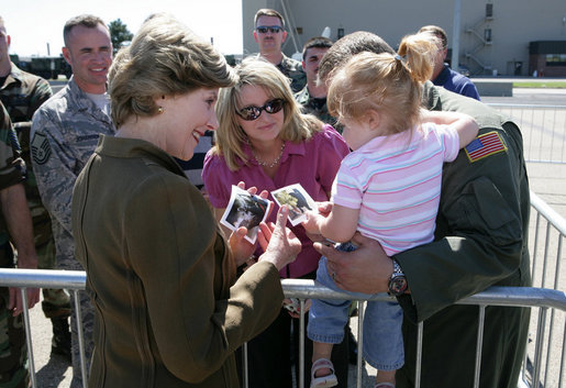 Mrs. Laura Bush offers photos of the Bush family dogs, Scottish Terrier's Barney and Miss Beazley, and the cat, Willie, to a little girl before departing from Forbes Field in Topeka, Kan., on Tuesday, Sept. 16, 2008. She had just greeted members of the military gathered to see her departure from the air field. White House photo by Chris Greenberg