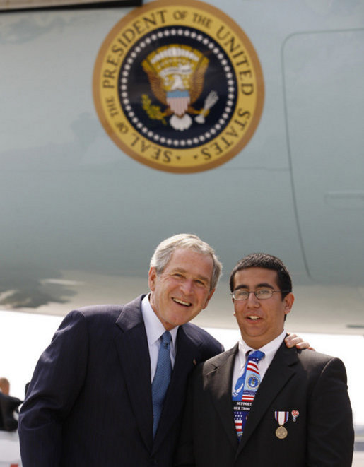 President George W. Bush embraces U.S. Freedom Corps volunteer Joey Rizzolo, Jr., of Paramus, N.J., on the President's arrival Monday, Sept. 22, 2008, to John F. Kennedy International Airport in New York. Rizzolo has been recognized as one of the top youth volunteers in America. White House photo by Eric Draper