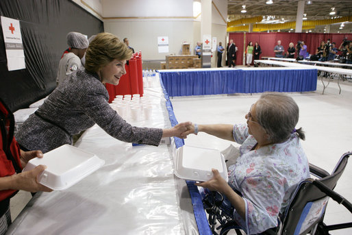Mrs. Laura Bush hands a meal to Hurricane Ike evacuee Barbara Woodarek Friday, Oct. 3, 2008, during her visit to the Auchan Red Cross Shelter in Houston for those individiuals and families still in need of assistance as a result of Hurricane Ike. White House photo by Chris Greenberg