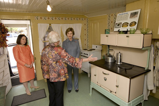 Mrs. Laura Bush receives an explanation of the scale of author Laura Ingalls Wilder's kitchen from Mrs. Jean Coday, Director and President of the Laura Ingalls Wilder Historic Home and Museum in Mansfield, Mo., Oct. 3, 2008. Accompanying the two on the tour is Mrs. Melanie Blunt, First Lady of Missouri. Wilder is one of Mrs. Bush's favorite writers and she was surprised to see the petite kitchen, built to function for the 4-foot-10-inch author. White House photo by Chris Greenberg