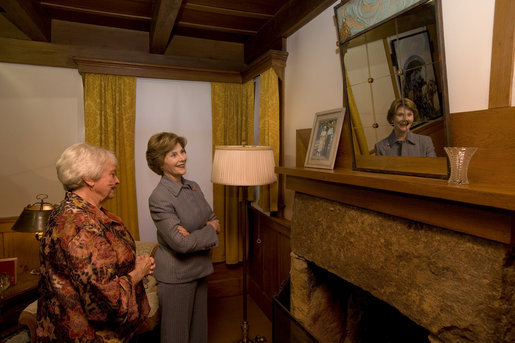 "Mrs. Laura Bush looks at a portrait of Laura Ingalls Wilder and her husband on the Wilder home mantle Oct. 3., 2008, in Mansfield, Mo. Laura Ingalls married Almanzo Wilder in the summer of 1885 and moved to the Mansfield home where the ""Little House"" book series was written in 1894. Mrs. Jean Cody, Director and President of the Laura Ingalls Wilder Historic Home and Museum, explains that the mantle was something that the author really wanted to have. Her husband objected but obviously finally gave in. Wilder, who has been read by children and adults for over 70 years, is one of Mrs. Bush's favorite authors. The visit was used to help encourage American's to read their classic literature which defines us as a nation, reflects our history and bring us together by expressing our shared ideals. White House photo by Chris Greenberg"