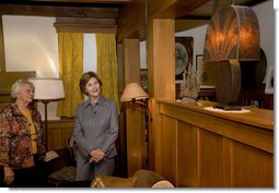Mrs. Laura Bush admires a steel lamp at the Mansfield, Mo., home of Laura Ingalls Wilder. Mrs. Jean Coday, Director and President of the Laura Ingalls Wilder Historic Home and Museum, explains that the lamp originally belonged to the well-known author's sister. This week the Laura Ingalls Wilder Historic Home and Museum was designated a Save America's Treasures project. White House photo by Chris Greenberg