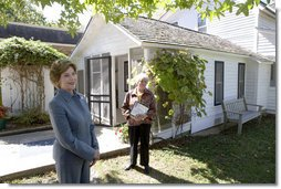 "Mrs. Laura Bush talks with press outside the Mansfield, Mo., home of author Laura Ingalls Wilder after Mrs. Jean Coday, Director and President of the Laura Ingalls Wilder Historic Home and Museum, offered the First Lady a tour of the modest home. The home was designated this week as a Save America's Treasures project, which is in partnership with the National Trust for Historic Preservation. Mrs. Bush noted that Wilder, who wrote the ""Little House"" book series, was one of her favorite authors. ""My mother read them to me when I was little before I could read,"" she said. White House photo by Chris Greenberg"