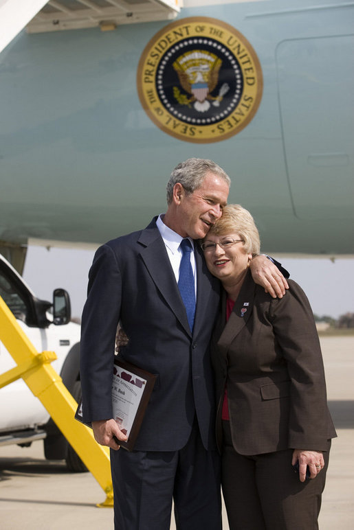 President George W. Bush embraces Freedom Corps greeter Nancy Arnold of Fairfield, Ohio, who President Bush honored with a Presidental Volunteer Service Award upon his arrival to Cincinnati/Northern Kentucky International Airport Monday, Oct. 6, 2008, in Hebron, Ky. White House photo by Eric Draper