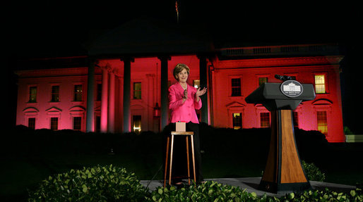 Mrs. Laura Bush applauds after pushing the button to flood the north front of the White House with a sea of pink, in honor of Breast Cancer Awareness Month, on Oct. 7, 2008. Bush addressed breast cancer survivors and advocates and members of the diplomatic corps just before the light display. The First Lady has encouraged worldwide efforts in preventing and curing a disease that is the leading cause of death in women. Each year more than 1.2 million people worldwide are diagnosed with breast cancer. The United States is working with countries in the Middle East, Europe and the Americas to empower women to take control of their health, raise awareness about the importance of prevention and early diagnosis, and support collaborative research to find a breast cancer cure. White House photo by Chris Greenberg