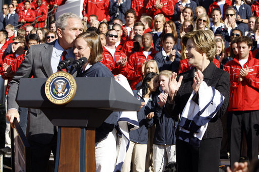 President George W. Bush kisses Army Lieutenant Melissa Stockwell, Paralympian and Iraq war veteran, after she presents President Bush and Mrs. Laura Bush with the American Flag that flew over the Olympic Village in Beijing following his remarks to members of the 2008 United States Summer Olympic and Paralympic Teams Tuesday, Oct. 7, 2008, on the South Lawn of the White House. White House photo by Eric Draper