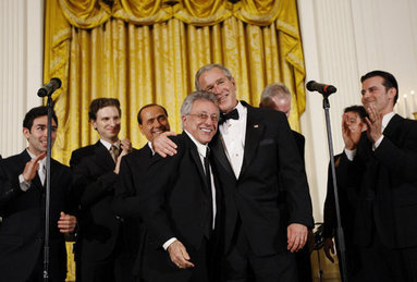 President George W. Bush, joined on stage by Italian Prime Minister Silvio Berlusconi, embraces singer Frankie Valli, lead singer of The Four Seasons, invited on stage Monday evening, Oct. 13, 2008, following a performance of the Broadway cast of the Jersey Boys in the East Room of the White House. White House photo by Eric Draper