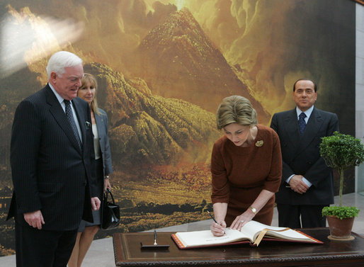 Mrs. Laura Bush signs the guest book Oct. 13, 2008 at the National Gallery of Art in Washington as Italian Prime Minister Silvio Berlusconi waits to sign as well. At left is Mr. Rusty Powell, Director of the National Gallery of Art, who led the tour. The Mt. Vesuvius mural is one of the backdrops for the exhibit. White House photo by Joyce N. Boghosian