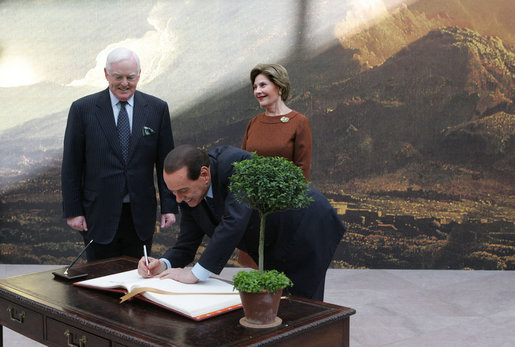 "Italian Prime Minister Silvio Berlusconi follows Mrs. Laura Bush in signing the guest book Oct. 13, 2008 at the National Gallery of Art in Washington At left is Mr. Rusty Powell, Director of the National Gallery of Art, who led a tour of the exhibit ""Pompeii and the Roman Villa; Art and Culture Around the Bay of Naples."" The Mt. Vesuvius mural one of the backdrops for the exhibit. White House photo by Joyce N. Boghosian"