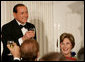Prime Minister Silvio Berlusconi of Italy, seated next to Mrs. Laura Bush, acknowledges a toast offered in his honor by President George W. Bush Monday evening, Oct. 13, 2008, at the White House State Dinner in honor of Berlusconi's visit to Washington, D.C. White House photo by Chris Greenberg