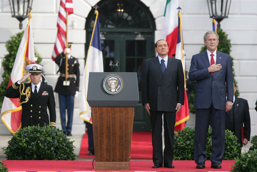 President George W. Bush and Prime Minister Silvio Berlusconi stand together on the reviewing stand Monday, Oct. 13, 2008 on the South Lawn of the White House, during the playing of the National Anthem. White House photo by Chris Greenberg
