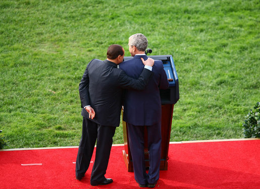 President George W. Bush is embraced by Prime Minister Silvio Berlusconi as he honors the Italian leader Monday, Oct. 13, 2008, during an official welcoming ceremony on the South Lawn of the White House. White House photo by Grant Miller