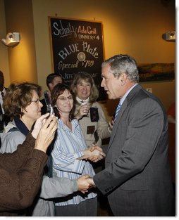 President George W. Bush greets diners Wednesday, Oct. 15, 2008, at the Schnitz Ada Deli and Grill in Ada, Michigan. The President met with business owners from the Grand Rapids area over lunch at the deli to talk about the economy. White House photo by Eric Draper