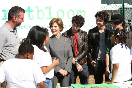 Surrounded by children participating in a soil sampling event, Mrs. Laura Bush speaks with Benjamin Jones, Director of Education, Trinity River Audubon Center, left during the First Bloom event at the Trinity River Audubon Center Sunday, November 2, 2008, in Dallas, TX. Mrs. Bush is joined by singer/songwriters the Jonas Brothers, Kevin Jonas, Joe Jonas, and Nick Jonas, right. White House photo by Chris Greenberg