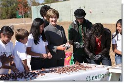 Surrounded by children Mrs. Laura Bush practices making seed balls during a First Bloom event at the Trinity River Audubon Center, Sunday, November 2, 2008, in Dallas, TX. Mrs. Bush is joined by singer/songwriters the Jonas Brothers, Kevin Jonas, Joe Jonas, and Nick Jonas, right.  White House photo by Chris Greenberg