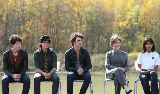 Mrs. Laura Bush is joined onstage by Boys and Girls Club student Jovanna Moreno age 11, right, and singer/songwriters the Jonas Brothers, Nick Jonas age 16, left, Joe Jonas age 19, 2nd from left, and Kevin Jonas age 20, 3rd left during a First Bloom event at the Trinity River Audubon Center, Sunday, November 2, 2008, in Dallas, TX. White House photo by Chris Greenberg
