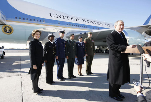 President George W. Bush, joined by Mrs. Laura Bush, stands outside Air Force One as he addresses his remarks in honor of Veterans Day, Tuesday, Nov. 11, 2008 upon the President's arrival at John F. Kennedy International Airport in New York. President Bush introduced military personnel representing the five branches of the armed services, who traveled with him aboard AF-1, honoring their service, from left are, U.S. Navy Chief Petty Officer Shenequa Cox of Dallas, Texas; U.S. Coast Guard Petty Officer First Class Christopher O. Hutto of Homer, Alaska; U.S. Army National Guard SSgt Michael Noyce-Merino of Melrose, Montana; U.S. Air Force Senior Airman Alicia Goetschel of Warrensburg, Mo., and U.S. Marine Corps Sgt. John Badon of Lufkin, Texas. White House photo by Eric Draper