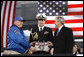 President George W. Bush is presented a piece of the flight deck of the USS Intrepid by Mike Hallahan, left, president of the United War Veterans Council of New York, also joined by military aide U.S. Navy Lt.Cmdr. Clay Beers, during the rededication ceremony Tuesday, Nov. 11, 2008, for the Intrepid Sea, Air and Space Museum in New York. White House photo by Eric Draper