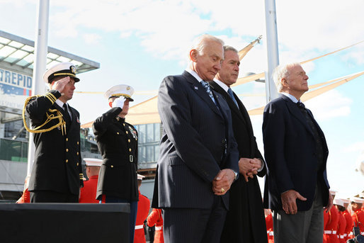 President George W. Bush, joined by former astronauts Edwin 'Buzz' Aldrin, left, and Scott Carpenter, stand together during a moment of silence after tossing a memorial wreath Tuesday, Nov. 11, 2008 from the deck of the USS Intrepid into the Hudson River, during a Veteran's Day tribute in New York. White House photo by Chris Greenberg