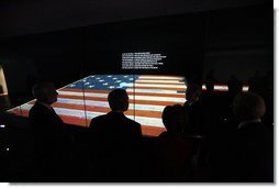 President George W. Bush is silhouetted against an American flag exhibit Wednesday, Nov. 19, 2008, during his visit with Mrs. Laura Bush to the National Museum of American History in Washington, D.C. White House photo by Eric Draper