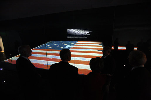 President George W. Bush is silhouetted against the renovated Star-Spangled Banner American flag exhibit Wednesday, Nov. 19, 2008, during his visit with Mrs. Laura Bush to the National Museum of American History in Washington, D.C. The flag, which flew above Fort McHenry in Baltimore during the British attack in 1814, inspired Francis Scott Key to write the lyrics that became our national anthem. White House photo by Eric Draper