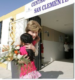 Mrs. Laura Bush hugs a young girl after she was presented with a bouquet of flowers upon her arrival welcome to the San Clemente Health Center Friday, Nov. 21, 2008, in San Clemente, Peru. Mrs. Bush visited the center and participated in interactive demonstrations depicting community-based health training. White House photo by Joyce N. Boghosian