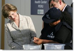 Mrs. Laura Bush looks on Friday, Nov. 21, 2008, as Ms. Maria Salguero Trillo, Community Health Educator Volunteer at the San Clemente Health Center in San Clemente, Peru, demonstrates how families are trained to treat contaminated water for safe drinking. In the town of 25,000, nearly 89 percent of the homes were affected by the August 2007, 8.0-magnitude earthquake. White House photo by Joyce N. Boghosian