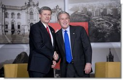 President George W. Bush and Prime Minister Stephen Harper of Canada smile for the cameras during a greeting Saturday, Nov. 22, 2008, prior to the their meeting in Lima, Peru. White House photo by Eric Draper