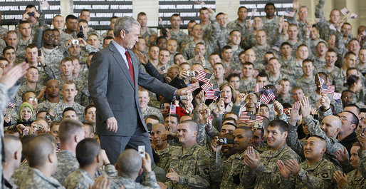 "President George W. Bush acknowledges his audience as he enters the staging area Tuesday, Nov. 25, 2008, at Fort Campbell, Ky., home of the 101st Airborne. The President told the troops, ""We are blessed to have defenders of such character and courage. I'm grateful to the families who serve by your side. And I will always be thankful for the honor of having served as the Commander-in-Chief."" White House photo by Eric Draper"