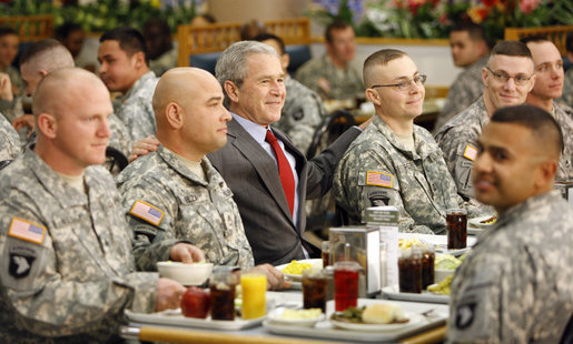 President George W. Bush is flanked by Sgt. First Class Rick Elza, left, of Lexington, Ky., and Capt. Rolando Perez of Mayaguez, Puerto Rico, as he sits for lunch Tuesday, Nov. 25, 2008, at Fort Campbell's Son Cafe. White House photo by Eric Draper