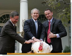 President George W. Bush stands between Paul Hill, left, of the National Turkey Federation, and his son, Nathan Hill during the pardoning of the Thanksgiving turkey Wednesday, Nov. 26, 2008, in the Rose Garden of the White House. This year marked the 61st anniversary of the National Thanksgiving Turkey Presentation and Pardoning.  White House photo by Joyce N. Boghosian