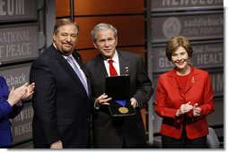 President George W. Bush, joined by Mrs. Laura Bush, is presented with the International Medal of PEACE by Pastor Rick Warren, Monday, Dec. 1, 2008, following their participation at the Saddleback Civil Forum on Global Health in Washington, D.C. White House photo by Eric Draper