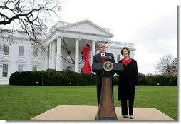 President George W. Bush and Mrs. Laura Bush address reporters on World AIDS Day from the the North Lawn of the White House, Monday, Dec. 1. 2008, where President Bush reaffirmed the commitment to fight HIV/AIDS at home and abroad. A large red ribbon is displayed from the North Portico of the White House in observance of World AIDS Day. White House photo by Joyce N. Boghosian