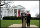 President George W. Bush and Mrs. Laura Bush address reporters on World AIDS Day from the North Lawn of the White House, Monday, Dec. 1. 2008, where President Bush reaffirmed the commitment to fight HIV/AIDS at home and abroad. A large red ribbon is displayed from the North Portico of the White House in observance of World AIDS Day. White House photo by Joyce N. Boghosian