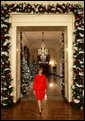 Mrs. Laura Bush walks from the White House Cross Hall into the East Room, Wednesday, Dec. 3, 2008, to begin the Christmas press preview of the White House decorations and preparations. White House photo by Chris Greenberg