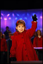 Four-year-old singer Kaitlyn Maher waves to the crowd during her performance Thursday, Dec. 4, 2008, at the Ellipse in Washington, D.C., for the annual Lighting of the National Christmas Tree. White House photo by Eric Draper