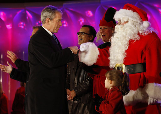 President George W. Bush exchanges knuckles with Santa Thursday, Dec. 4, 2008, during the 2008 Lighting of the National Christmas Tree Ceremony on the Ellipse in Washington, D.C. It is the 85th year of the ceremony that began during the Coolidge Administration. White House photo by Eric Draper
