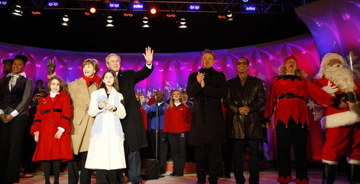 President George W. Bush and Mrs. Laura Bush stand on stage Thursday, Dec. 4, 2008, with Santa, entertainers and guests, during the 85th Lighting of the National Christmas Tree on the Ellipse in Washington, D.C. With them, from left, are: Members of Step Afrika!; Lindsey Van Horn, 9, and Kayleigh Kepler, 11, the official tree lighters; Phil Vassar; Jon Secada, and Santa and his elf. White House photo by Eric Draper