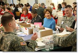 "Mrs. Laura Bush joins military and civilian volunteers Saturday, Dec. 6, 2008, as she signs and sorts seasonal cards written for U.S. troops at the American Red Cross Holiday Mail for Heroes event. Seated next to Mrs. Bush at Red Cross headquarters in Washington, D.C., is young volunteer Tre'shaad ""Tre"" Cox, age 11, with American Red Cross President and CEO Gail McGovern at the end of the table, in red. At very far right is Bonnie McElveen-Hunter, Chairman of the American Red Cross. In the room full of volunteers, Mrs. Bush reminded Americans that they have until December 10th to send a holiday card at designated post office boxes for the troops deployed around the world.  White House photo by Chris Greenberg"