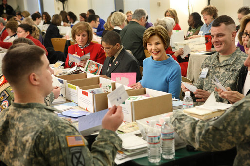 "Mrs. Laura Bush is seated between volunteers Master Tre'shaad Cox, 11, left, and U.S. Army Sgt. Thomas Griffin, an out-patient at Walter Reed Army Medical Center, during a visit Saturday, Dec. 6, 2008, to the American Red Cross Holiday Mail for Heroes Packing Event at the Red Cross National Headquarters in Washington, D.C. Mrs. Bush reminded the volunteers that during this holiday season, ""we are reminded of our many blessings, especially our freedom. The American Red Cross Holiday Mail for Heroes project, in partnership with Pitney Bowes, provides citizens an opportunity to send holiday cards to members of our Armed Forces. I am grateful to the many volunteers gathered here today to ensure our military receives our message of thanks for the sacrifice they make each day to defend our freedom."" White House photo by Chris Greenberg"