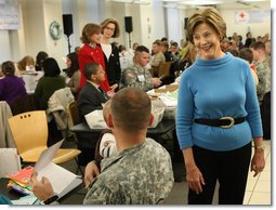 Mrs. Laura Bush greets one of the military volunteers and his child during the Saturday, Dec. 6, 2008, American Red Cross Holiday Mail for Heroes event in Washington, D.C. Standing in the background are American Red Cross President and CEO Gail McGovern, in red, and Bonnie McElveen-Hunter, Chairman of the American Red Cross. As the room full of volunteers sorted cards created by Americans to send to U.S. troops deployed around the world, Mrs. Bush encouraged Americans to do volunteer work in their home towns for those in need of food, care or appreciation. Cards for the troops can still be sent until December 10th at designated post office boxes.  White House photo by Chris Greenberg