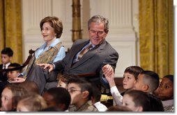 President George W. Bush, sitting with Mrs. Laura Bush, reaches to hold the hand of a young child Monday, Dec. 8, 2008 in the East Room of the White House, during the Children's Hoilday Reception and Performance.  White House photo by Eric Draper