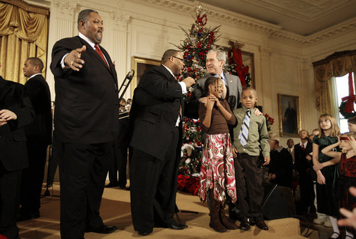 President George W. Bush is joined by two children on stage in the East Room of the White House as he thanks members of the musical group Sweet Heaven Kings, Monday, Dec. 8, 2008, during the Children's Holiday Reception and Performance. White House photo by Eric Draper