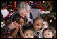 President George W. Bush embraces a group of youngsters Monday, Dec. 8, 2008, as he welcomes children attending the Children's Holiday Reception and Performance at the White House. White House photo by Eric Draper
