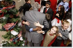 President George W. Bush is smothered in little hands as he says goodbye to a group of children in attendance Monday, Dec. 8, 2008, for the Children's Holiday Reception and Performance at the White House. The President and Mrs. Laura Bush traditionally invite children to a White House celebration for the holidays, and this year, the audience included kids of active duty and reserve military service members from Russell Elementary at Quantico Marine Base, Dahlgren School at Dahlgren Navy Base and West Meade Elementary at Ft. Meade Army Base.  White House photo by Eric Draper