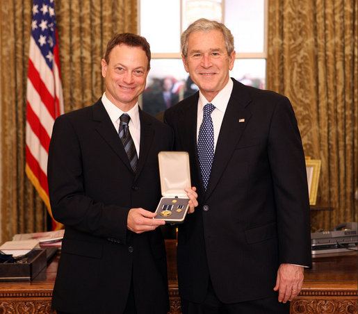 President George W. Bush stands with Gary Sinise after presenting him with the 2008 Presidential Citizens Medal Wednesday, Dec. 10, 2008, in the Oval Office of the White House. White House photo by Chris Greenberg