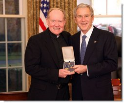 President George W. Bush stands with Father Tim Scully, CSC, after presenting him with the 2008 Presidential Citizens Medal Wednesday, Dec. 10, 2008, in the Oval Office of the White House.  White House photo by Chris Greenberg